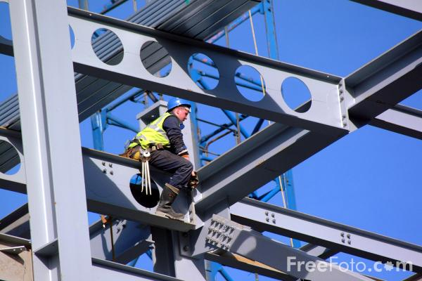 Male construction worker sitting on a gray steel beam in the air and surrounded by stell beams